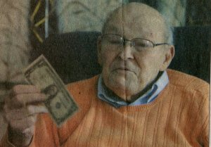Frank Morris displays dollar bill autographed by Vinegar Joe Stilwell